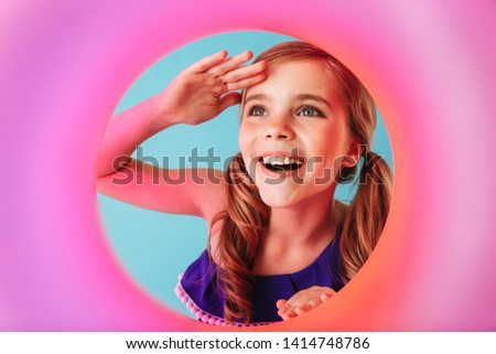 Cheerful little girl wearing swimsuit standing isolated over blue background, playing with inflatable ring #1414748786