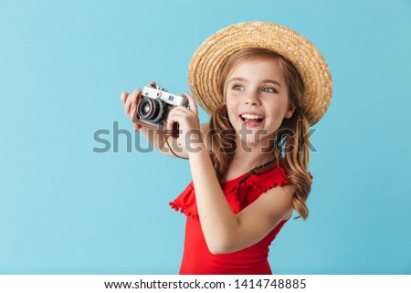 Cheerful little girl wearing swimsuit and summer hat standing isolated over blue background, taking picture with photo camera