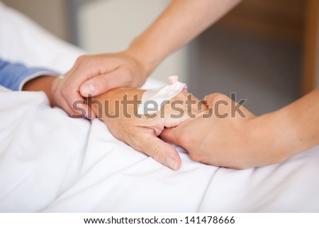 Closeup of nurse holding patients hand in hospital #141478666