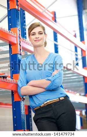 Portrait of a confident business woman relaxing next to shelve racks in warehouse #141479734