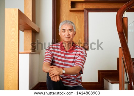 Portrait of Asian senior man sitting and resting on staircase of his modern house and looking at camera #1414808903