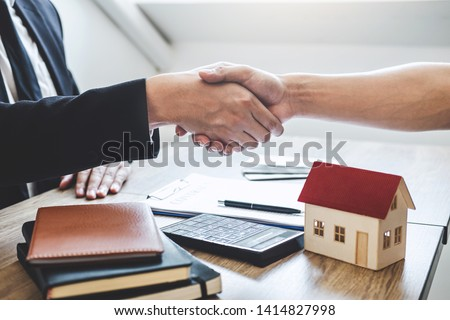 Finishing to successful deal of real estate, Broker and client shaking hands after signing contract approved application form, concerning mortgage loan offer for and house insurance. #1414827998