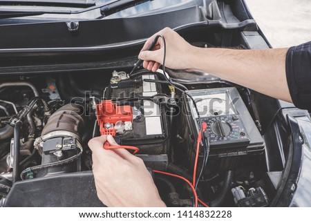 Services car engine machine concept, Automobile mechanic repairman hands checking a car engine automotive workshop with digital multimeter testing battery, car service and maintenance. #1414832228