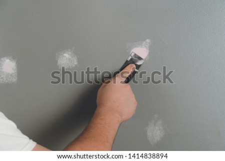 Man Spackling and Sanding Wall Preparing To Paint #1414838894
