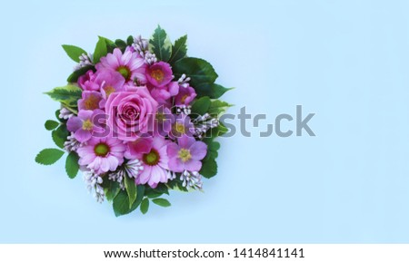Spring composition of yellow and pink chrysanthemums and roses on a light blue paper background with a copy of the space. Pastel colors. The view from the top. Background for greetings, invitations #1414841141