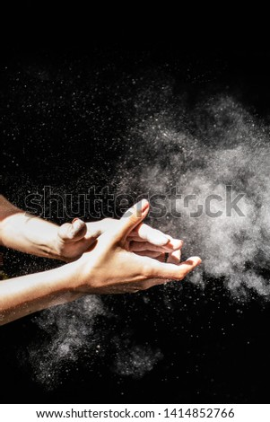 Close up of chalking hands with magnesium powder spreading in the air on black background with an athlete, natural light  #1414852766