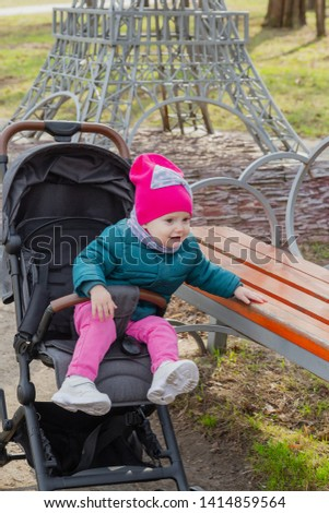 Little girl sitting in a baby carriage on the street #1414859564