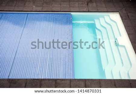 Swimming pool cover detail for protection and heat the water, pool roller-shutter covers close-up #1414870331