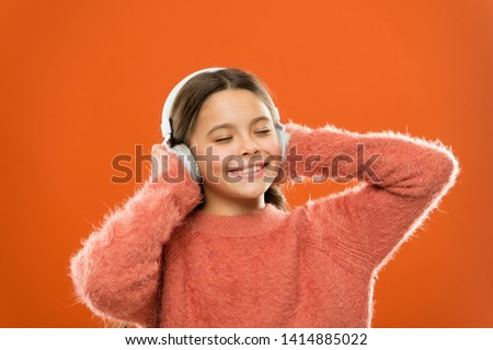 Make outside noise quieter and music sound better. Little girl relaxing with melodious sound. Cute kid listening to sound track in headphones. Small child enjoy electronic sound playing in earphones. #1414885022
