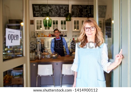 Shot of middle aged small business owner woman wearing apron and smiling to you while waiting for her guest in her coffee shop. Family business.  #1414900112