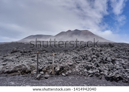 Landscape Picture of Mount Etna, active volcano in Sicily, Italy during cold and windy spring day. Black lava slope field under the top of volcano with main crater, Etna is highest volcano in Europe.
