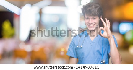 Young doctor wearing medical uniform over isolated background smiling positive doing ok sign with hand and fingers. Successful expression. #1414989611
