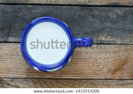 Blue cup of milk on wooden background #1415014208