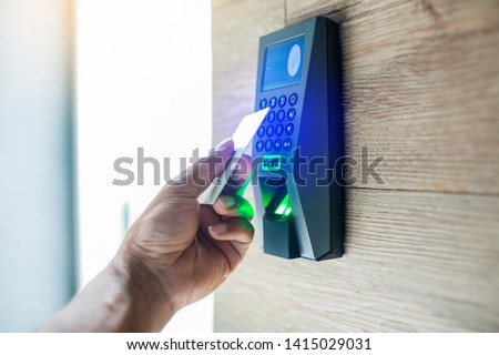 Door access control. Staff holding a key card to lock and unlock door at home or condominium. using electronic card key for access. electronic key and finger scan access control system to unlock doors #1415029031