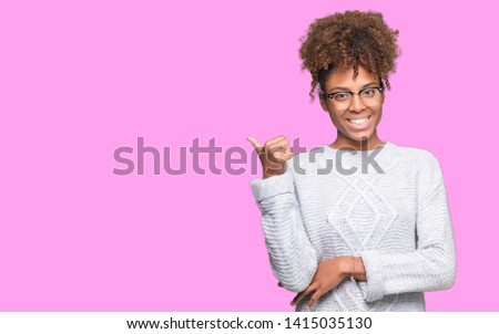 Beautiful young african american woman wearing winter sweater over isolated background smiling with happy face looking and pointing to the side with thumb up. #1415035130