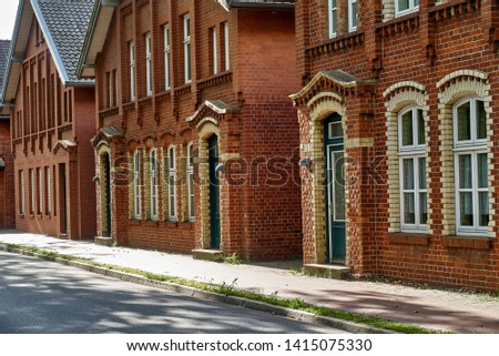 row of facades of traditional red brick houses with windows and doors next to a sidewalk of a street in Delmenhorst (Germany) on a sunny day Royalty-Free Stock Photo #1415075330