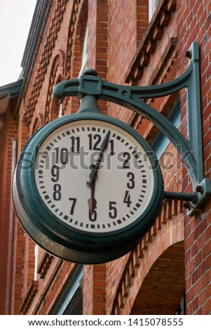 big vintage clock hangs at a red brick facade in Delmenhorst (Germany), it shows three minutes after six Royalty-Free Stock Photo #1415078555