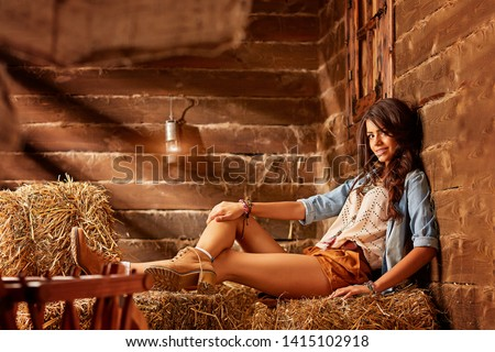 A young cowgirl sits on a bale of hay in a barn and smiles into the camera. a brunette girl is wearing short shorts, brown boots and a denim shirt #1415102918
