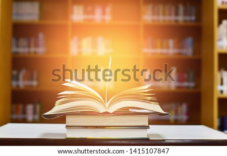 Open Book on wood table and blurred bookshelf in the library, education background, back to school concept. #1415107847