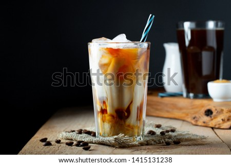 Ice coffee in a tall glass with cream poured over, ice cubes and beans on a old rustic wooden table. Cold summer drink with tubes on a black background with copy space #1415131238