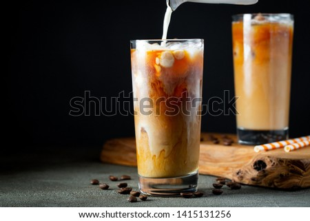Ice coffee in a tall glass with cream poured over, ice cubes and beans on a old rustic wooden table. Cold summer drink with tubes on a black background with copy space #1415131256