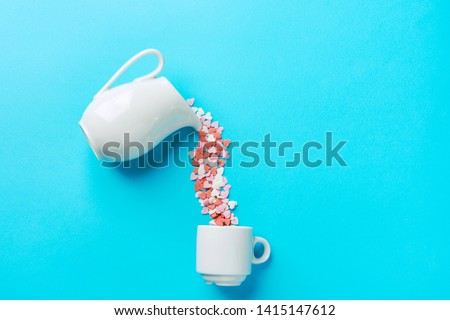 Multicolored sugar candy hearts imitating pouring liquid coffee tee from white milk jug pitcher into cup. Creative food flat lay. Charity love donation generosity concept. Placeholder with copy space