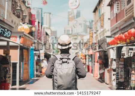 Young man hipster traveling with backpack and hat, happy Solo traveler walking at Chinatown street market in Singapore. landmark and popular for tourist attractions. Southeast Asia Travel concept Royalty-Free Stock Photo #1415179247