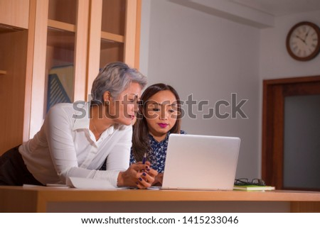 Executive Women coworking . Natural office lifestyle portrait of two work colleagues or business partners working together reading on laptop computer in job cooperation and collaboration  #1415233046
