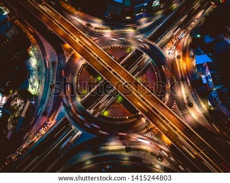 Aerial view of Morden city and smart transportation with Expressway, Road and Roundabout, busy highway traffic night time. Important infrastructure. #1415244803