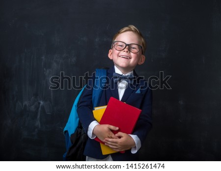 Cute child in school uniform and glasses. Go to school for the first time. Child with school bag and book. Kid indoors of the class room with blackboard on a background. Back to school #1415261474