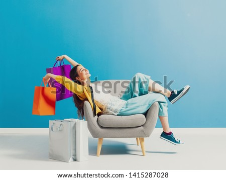 Cheerful happy shopaholic woman with lots of shopping bags, she is sitting on an armchair and celebrating with arms raised #1415287028