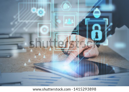Hand of man in suit using tablet computer in office with double exposure of online security interface and social media icons. Concept of data protection. Toned image #1415293898