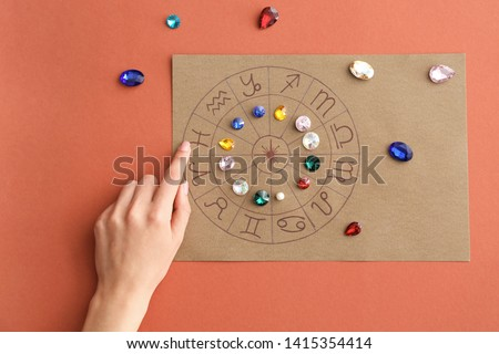 Astrological horoscope with birthstones and female hand on color background #1415354414