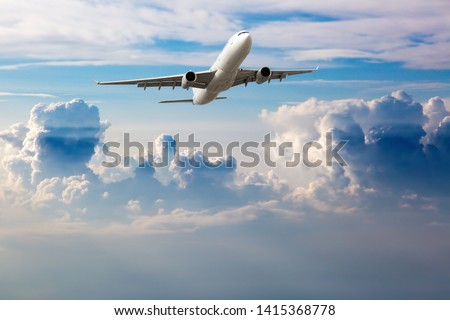 White passenger plane in flight. Aircraft flying high in the blue sky above the clouds. The aircraft is located at the top of the frame. #1415368778