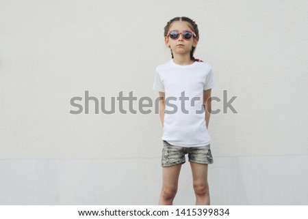 Kid girl wearing white t-shirt with space for your logo or design in casual urban style #1415399834