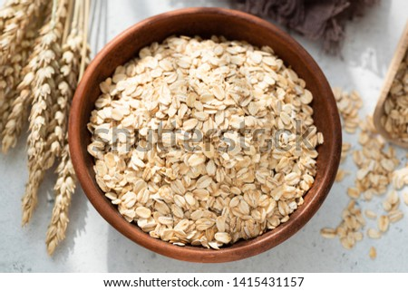 Oats or Oat Flakes in bowl, grey concrete background, top view. Healthy eating concept, weight loss and dieting #1415431157