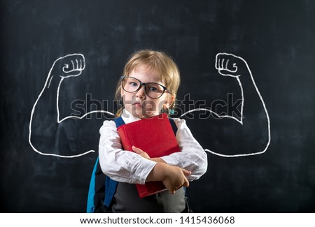 Cute child girl in school uniform and glasses. Go to school for the first time. Child with school bag and book. Kid in class room near chalkboard with muscles on it. Back to school #1415436068