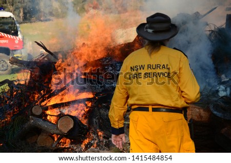 NSW RURAL FIRE SERVICE, with backburning and firetruck in background #1415484854