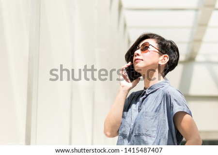 A beautiful stylish asian woman talking on the smartphone outside the building. She wearing 100% UV protection sunglasses to protect her eyes from sun rays. UVA UVB concerning, Skin care sunscreen. #1415487407