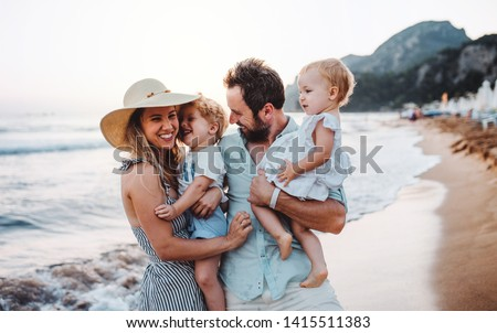 A young family with two toddler children standing on beach on summer holiday. #1415511383