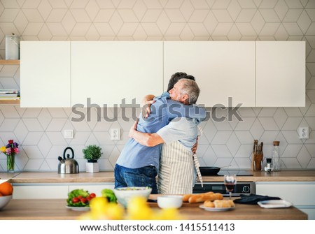 An adult hipster son and senior father indoors at home, hugging when cooking. #1415511413