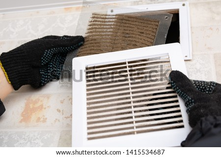 repair service man removing a dirty air filter on a house so he can replace it with a new clean. Extremely dirty and dusty white plastic ventilation air grille at home close up, harmful for health  #1415534687