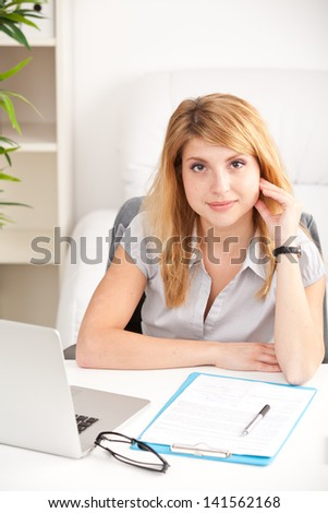 happy business woman sitting, thinking and working on laptop computer at office #141562168