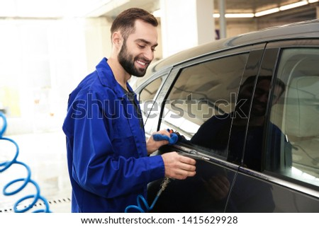 Worker cleaning automobile with gun and rag at car wash #1415629928
