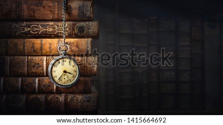 Vintage clock hanging on a chain on the background of old books. Old watch as a symbol of passing time. Concept on the theme of history, nostalgia, old age. Retro style. Royalty-Free Stock Photo #1415664692