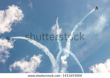 Photo of 3 airplanes in the sky with smoke behind of them. Photo was made on airshow.