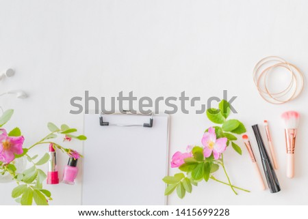 Flat lay blogger or freelancer workspace with a clipboard, pink flowers and green leaves on a white background #1415699228