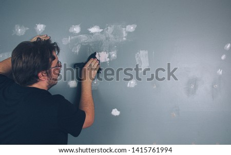Man Spackling and Sanding Wall Preparing To Paint #1415761994