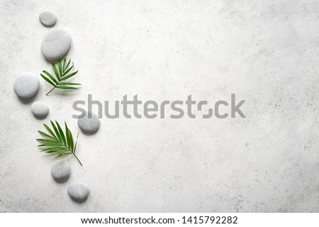 Spa concept on white stone background, palm leaves and zen like grey stones, top view, copy space.