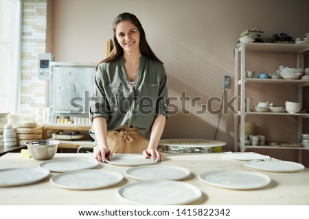 Portrait of smiling female artisan arranging handmade ceramic plates in pottery workshop, copy space #1415822342